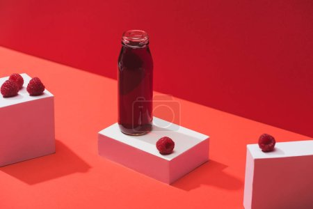 fresh berry juice in glass bottle near ripe raspberries on cubes on red background