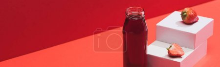 Photo for Fresh berry juice in glass bottle near ripe strawberry on cubes on red background, panoramic shot - Royalty Free Image