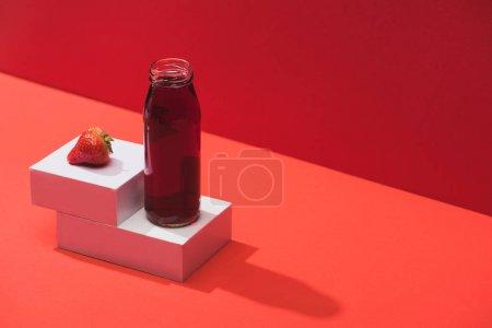 Photo pour Jus de baies frais en bouteille de verre près de fraise mûre sur cubes sur fond rouge - image libre de droit
