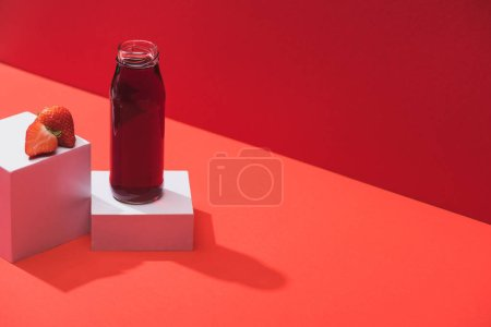 Photo for Fresh berry juice in glass bottle near ripe strawberry on cubes on red background - Royalty Free Image