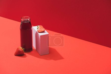 Photo for Fresh berry juice in glass bottle near ripe strawberries on cube on red background - Royalty Free Image