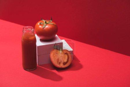 Photo pour Jus de légumes frais en bouteille de verre près de tomates mûres sur cubes sur fond rouge - image libre de droit