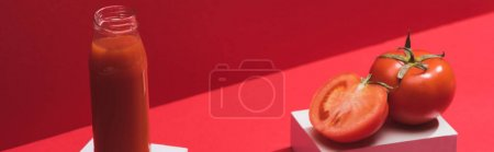 Photo pour Jus de légumes frais en bouteille en verre et tomates mûres sur cubes sur fond rouge, panoramique - image libre de droit
