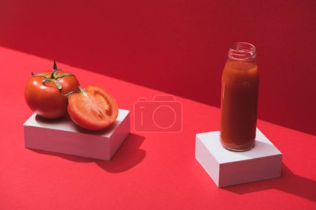 Photo for Fresh vegetable juice in glass bottle and ripe tomatoes on cubes on red background - Royalty Free Image