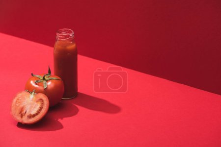 fresh vegetable juice in glass bottle and ripe tomatoes on red background