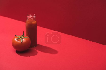 fresh vegetable juice in glass bottle and ripe tomato on red background