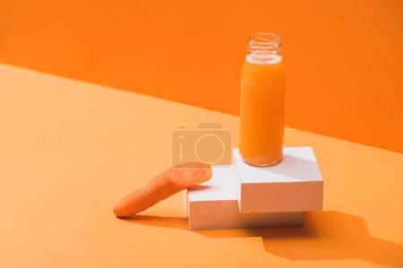 Photo pour Jus frais en bouteille de verre près de carotte mûre sur cubes sur fond orange - image libre de droit