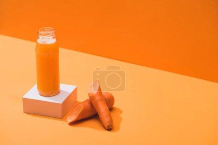 Photo for Fresh juice in glass bottle on cube near ripe carrots on orange background - Royalty Free Image