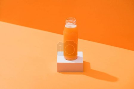 fresh carrot juice in glass bottle on cube on orange background