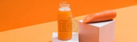 Photo pour Jus frais en bouteille de verre près de carotte mûre sur cubes sur fond orange, panoramique - image libre de droit