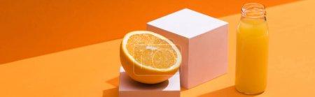 Photo pour Jus frais en bouteille de verre près de la moitié orange et cubes blancs sur fond orange, panoramique - image libre de droit