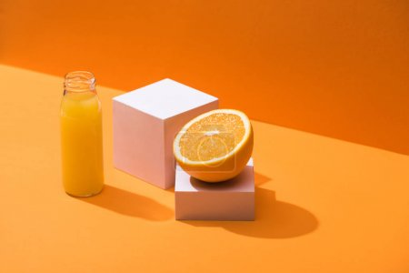 Photo for Fresh juice in glass bottle near orange half and white cubes on orange background - Royalty Free Image