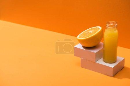 Photo pour Jus frais en bouteille de verre près de la moitié orange et cubes blancs sur fond orange - image libre de droit