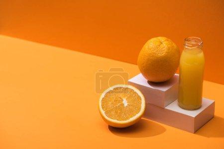 Photo for Fresh juice in glass bottle near oranges and white cubes on orange background - Royalty Free Image