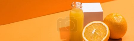 fresh juice in glass bottle near oranges and white cube on orange background, panoramic shot