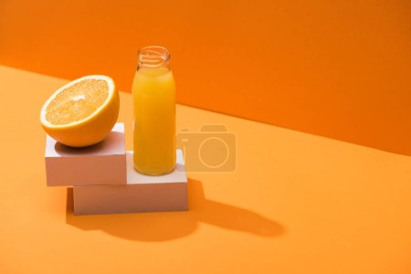 Photo for Fresh juice in glass bottle near orange half and white cubes on orange background - Royalty Free Image