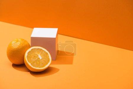 Photo pour Oranges fraîches et cube blanc sur fond orange - image libre de droit