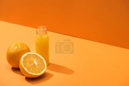 Photo for Fresh juice in glass bottle near oranges on orange background - Royalty Free Image