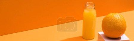 Photo pour Jus frais en bouteille de verre près de cube orange et blanc sur fond orange, panoramique - image libre de droit
