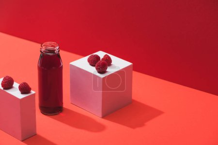 Photo for Fresh berry juice in glass bottle near ripe raspberries on cubes on red background - Royalty Free Image