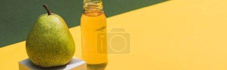 Photo pour Jus frais en bouteille près de poire et cube blanc sur fond vert et jaune, photo panoramique - image libre de droit