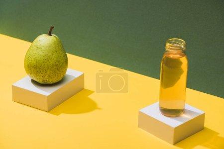 Photo pour Jus frais en bouteille près des cubes poires et blancs sur fond vert et jaune - image libre de droit