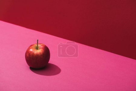 Photo for Fresh juicy apple on red and pink background - Royalty Free Image