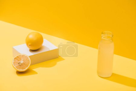 fresh juice in bottle near lemons and white cube on yellow background