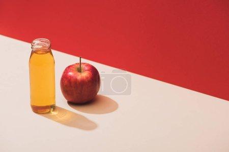 Photo pour Jus frais en bouteille près de pomme sur fond rouge - image libre de droit