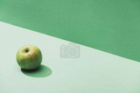 Photo pour Pomme entière fraîche sur fond vert et turquoise - image libre de droit