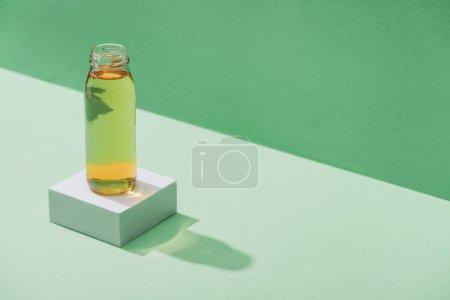 Photo pour Jus de pomme frais sur cube blanc sur fond vert et turquoise - image libre de droit