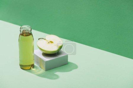 Photo pour Jus frais près de la moitié pomme et cube blanc sur fond vert et turquoise - image libre de droit