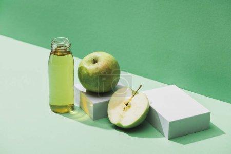 Photo pour Jus frais près des pommes et des cubes blancs sur fond vert et turquoise - image libre de droit