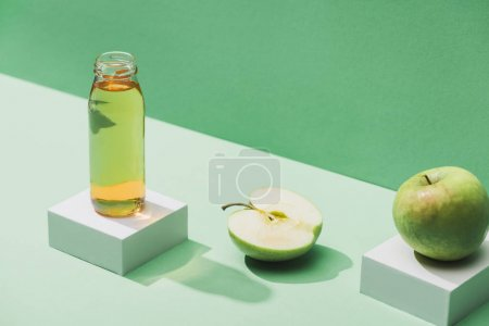 Photo for Fresh juice near apples and and white cubes on green and turquoise background - Royalty Free Image
