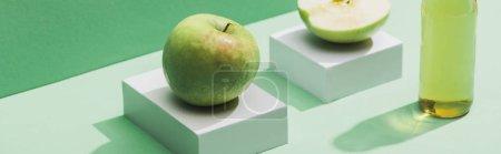 Photo pour Jus frais près des pommes et des cubes blancs sur fond vert et turquoise, panoramique - image libre de droit