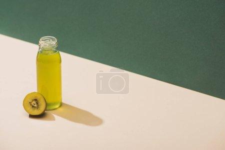 Photo pour Jus frais près de kiwi sur fond vert et blanc - image libre de droit