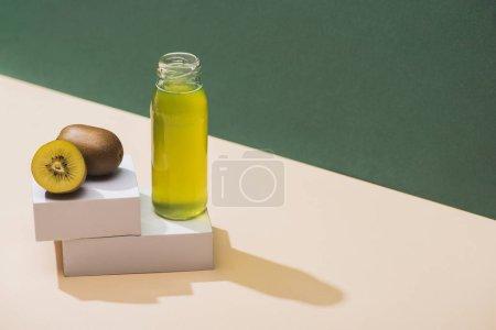 Photo pour Jus frais près des kiwis et cubes blancs sur fond vert et blanc - image libre de droit