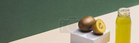 Photo pour Jus frais près des kiwis et cubes blancs sur fond vert et blanc, photo panoramique - image libre de droit