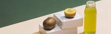 Photo pour Jus frais près de kiwi et cubes blancs sur fond vert et blanc, panoramique - image libre de droit