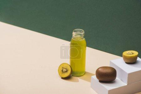 Photo pour Jus frais près de kiwi et cubes blancs sur fond vert et blanc - image libre de droit
