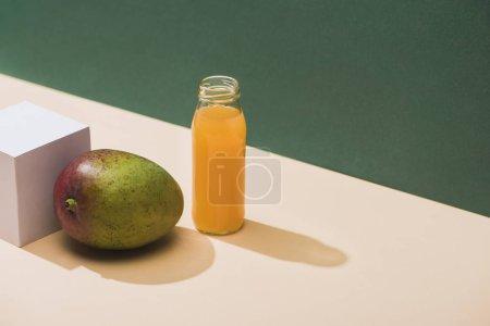 Photo pour Jus frais en bouteille près de mangue et cube blanc sur fond vert - image libre de droit