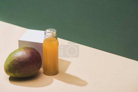Photo pour Jus frais en bouteille près de la mangue et cube blanc sur fond vert - image libre de droit