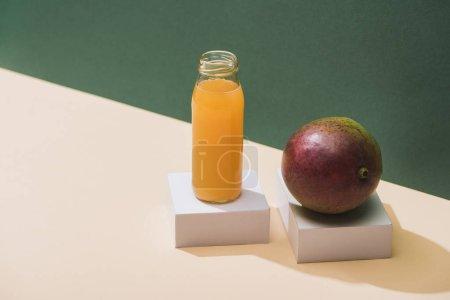 Photo pour Jus frais en bouteille près de la mangue et cubes blancs sur fond vert - image libre de droit