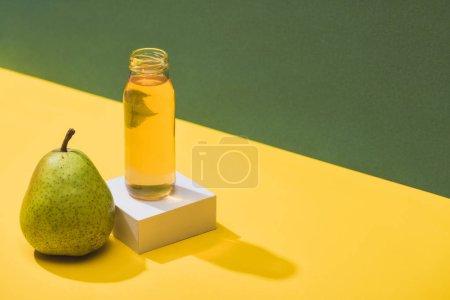 Photo pour Jus frais en bouteille près de la poire et cube blanc sur fond vert et jaune - image libre de droit