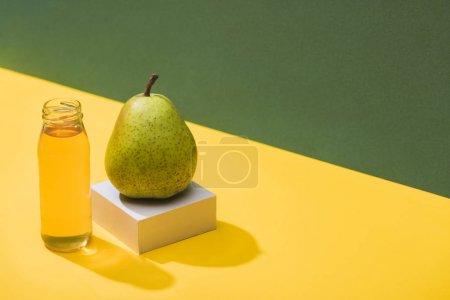 Photo pour Jus frais en bouteille près de poire et cube blanc sur fond vert et jaune - image libre de droit