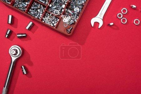 Photo pour Vue du dessus des clés avec boîte à outils et buses sur fond rouge - image libre de droit
