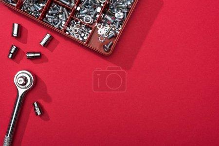 Photo pour Vue du dessus de la clé avec buses et boîte à outils avec boulons et écrous sur fond rouge - image libre de droit