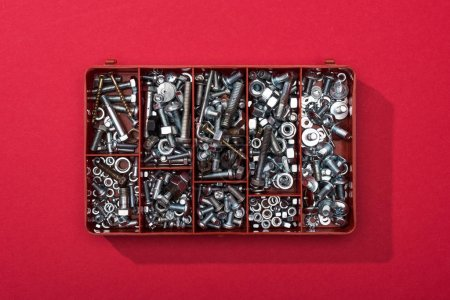 Photo for Top view of metal nuts and wood screws in tool box on red background - Royalty Free Image