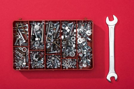 Top view of toolbox with nuts and bolts near wrench on red background