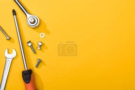 Photo pour Vue de dessus des clés, tournevis et boulons sur fond jaune - image libre de droit